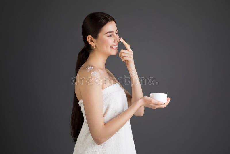 Cuidado de pele Frasco da bomba para o creme de face Mulher moreno de sorriso bonita com uma toalha de banho imagens de stock