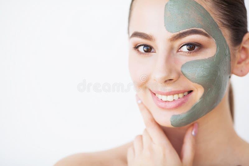 Cuidado de pele Jovem mulher com a máscara cosmética da argila que guarda o pepino imagens de stock royalty free