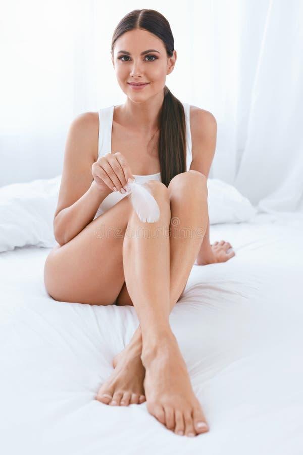 Cuidado de pele Mulher com a pele macia do corpo que toca nos pés com pena imagens de stock royalty free