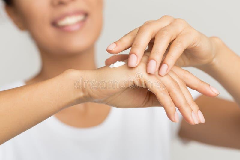 Cuidado de pele Mulher feliz que aplica o creme hidratando da mão fotos de stock royalty free