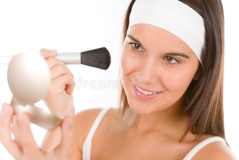 Cuidado de pele - a mulher nova aplica o pó foto de stock royalty free