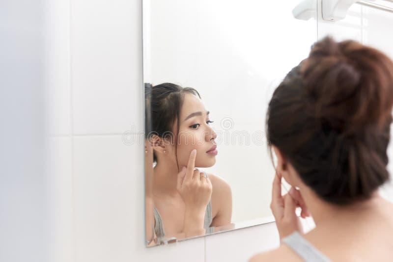 Cuidado de pele Mulher que aplica o creme de pele em sua cara na frente do espelho fotografia de stock royalty free