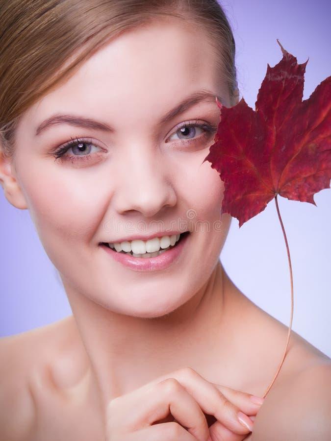 Cuidado de pele Retrato da menina da jovem mulher com folha de bordo vermelha fotografia de stock
