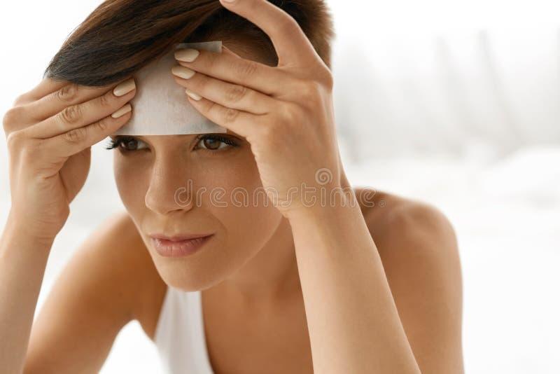 Cuidado de piel Cara de la limpieza de la mujer con los papeles absorbentes del aceite imagenes de archivo