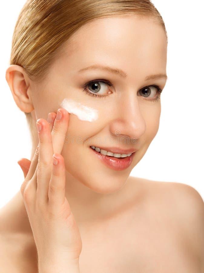 Cuidado de piel. cara de la mujer sana hermosa con la crema aislada imagenes de archivo
