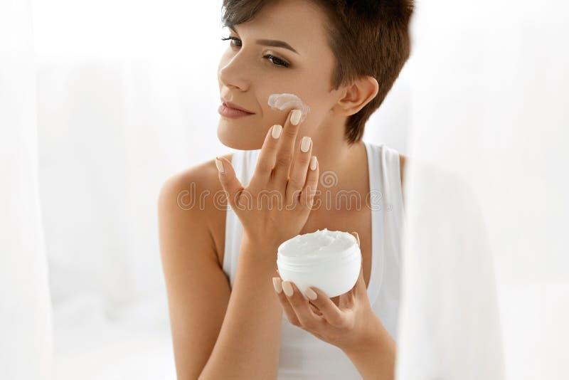 Cuidado de piel de la belleza Mujer hermosa que aplica la crema de cara cosmética imagenes de archivo