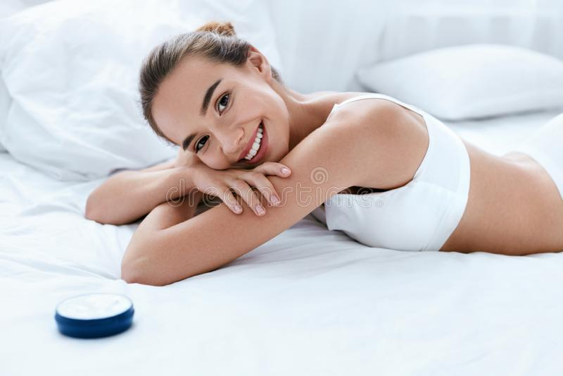Cuidado de piel del cuerpo de la mujer Muchacha sonriente hermosa con crema foto de archivo
