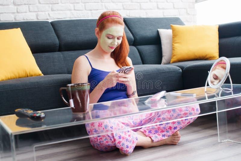 Cuidado de piel del tratamiento de la belleza para el texto de la mensajería de la muchacha en el teléfono fotos de archivo