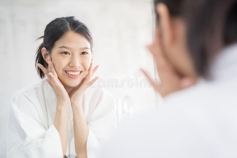 Cuidado de piel femenino Mujer asiática joven que toca su cara y que mira para duplicar en cuarto de baño fotos de archivo