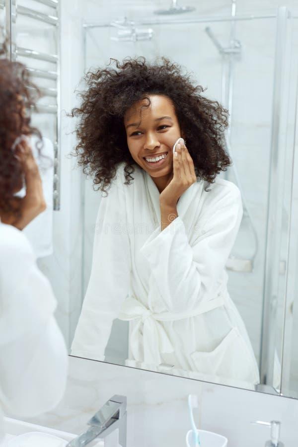 Cuidado de piel de la cara. Chica quitando maquillaje con toallita de algodón en el baño fotografía de archivo