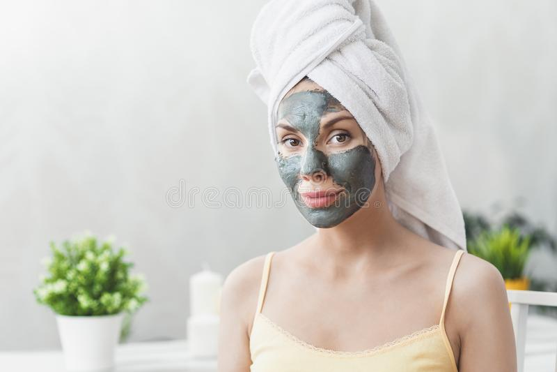 Cuidado de piel de la cara Mujer joven atractiva envuelta en la toalla de baño, aplicando la máscara del fango de la arcilla para fotografía de archivo