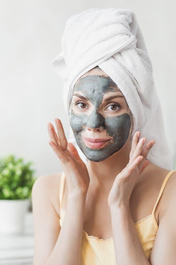 Cuidado de piel de la cara Mujer joven atractiva envuelta en la toalla de baño, aplicando la máscara del fango de la arcilla para foto de archivo