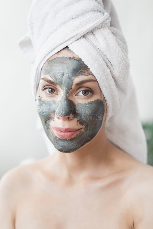 Cuidado de piel de la cara Mujer joven atractiva envuelta en la toalla de baño, aplicando la máscara del fango de la arcilla para imagen de archivo libre de regalías