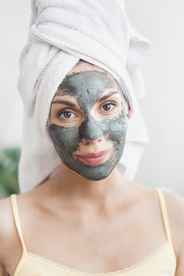 Cuidado de piel de la cara Mujer joven atractiva envuelta en la toalla de baño, aplicando la máscara del fango de la arcilla para imagen de archivo