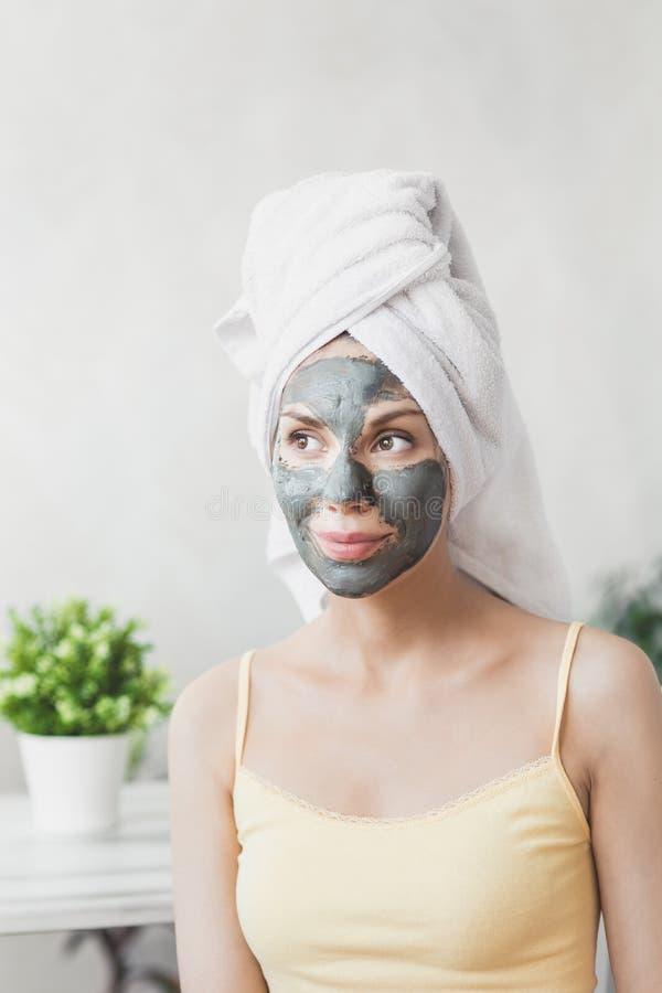 Cuidado de piel de la cara Mujer joven atractiva envuelta en la toalla de baño, aplicando la máscara del fango de la arcilla para fotos de archivo libres de regalías