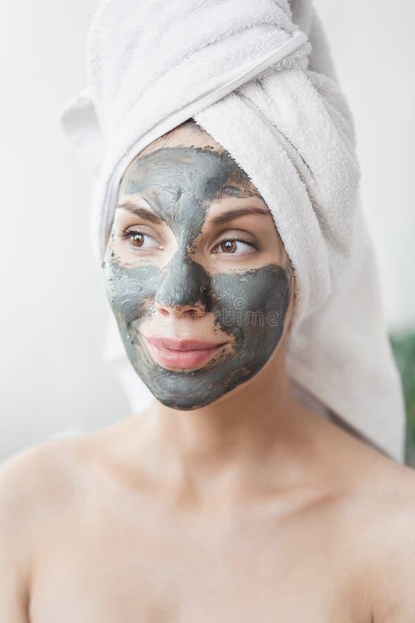Cuidado de piel de la cara Mujer joven atractiva envuelta en la toalla de baño, aplicando la máscara del fango de la arcilla para fotografía de archivo libre de regalías