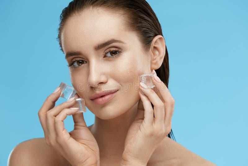 Cuidado de piel de la cara Mujer que aplica los cubos de hielo fotografía de archivo