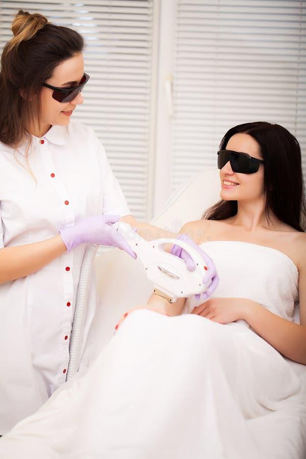Cuidado de piel Mujer adulta que tiene retiro del pelo del laser en salón de belleza profesional imágenes de archivo libres de regalías