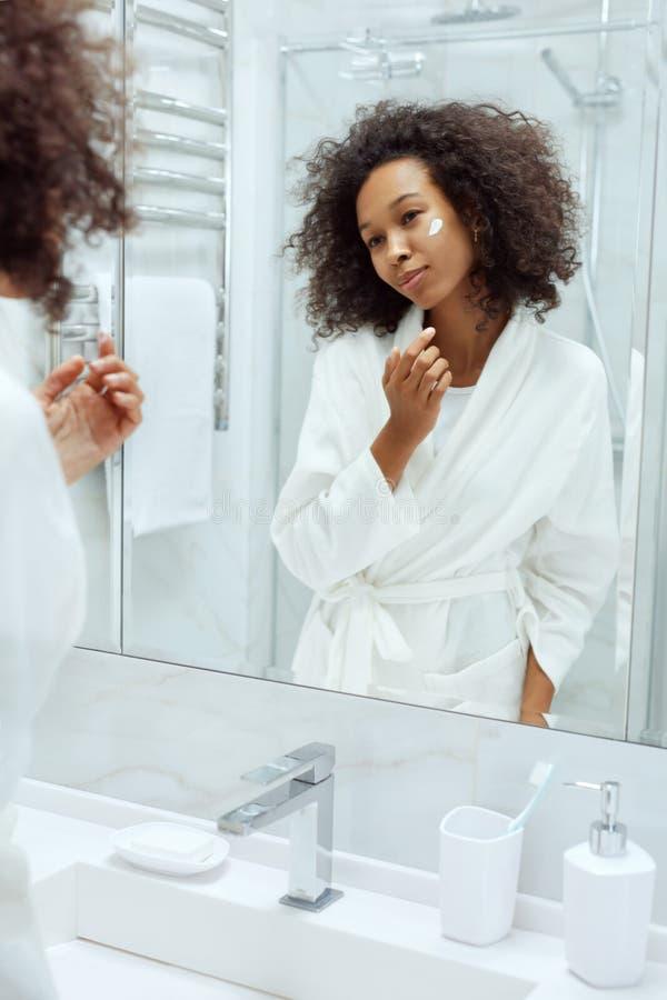 Cuidado de piel. Mujer aplicando crema facial mirando el espejo del baño foto de archivo