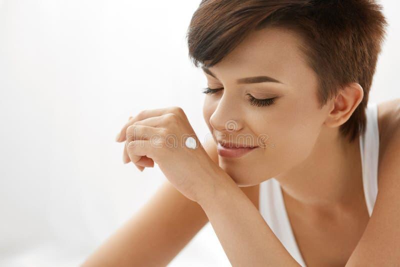 Cuidado de piel Mujer feliz hermosa con la loción de la crema de la mano en las manos fotos de archivo