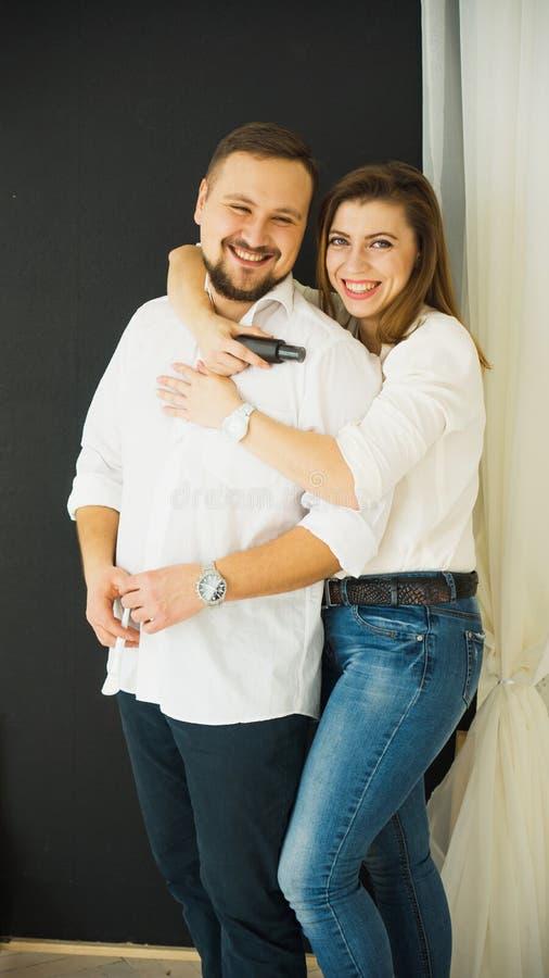 Cuidado de piel Mujer hermosa que abraza a un hombre alegre de risa joven, sosteniendo en sus manos una botella de crema de cara  fotografía de archivo libre de regalías