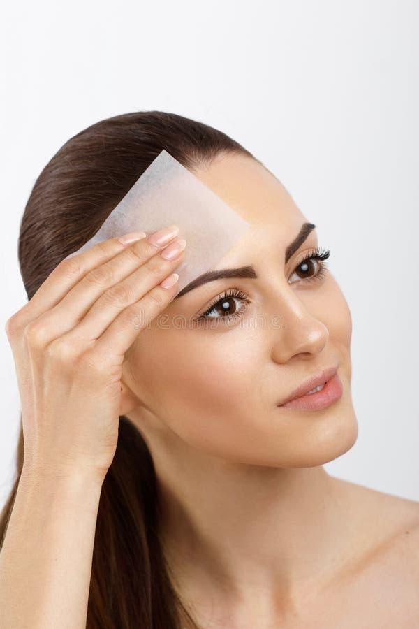 Cuidado de piel Mujer joven que quita el aceite de cara usando los papeles secantes Foto de la mujer hermosa con la piel lisa y s imagen de archivo libre de regalías