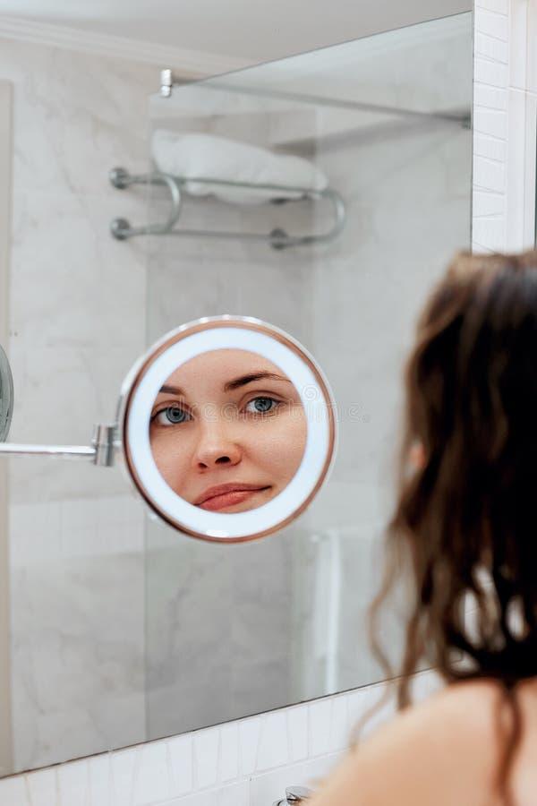 Cuidado de piel Mujer que toca el pelo y el rato sonriente que miran en el espejo Retrato de la muchacha feliz con el pelo mojado imagen de archivo