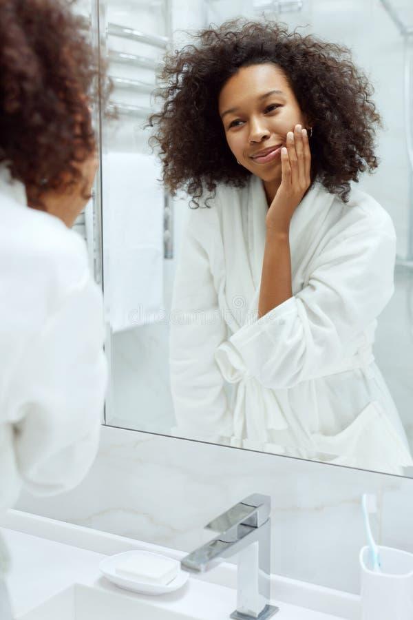Cuidado de piel. Mujer tocando la cara, mirando el espejo en el baño foto de archivo