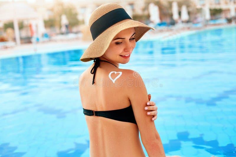 Cuidado de piel Protección de Sun La muchacha aplica la crema del sol Mujer con la loción del bronceado en la piscina en la forma foto de archivo