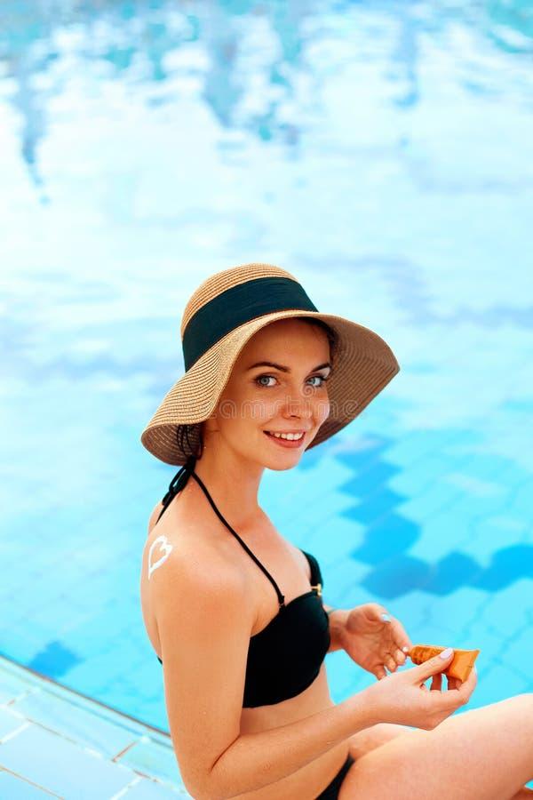 Cuidado de piel Protecci?n de Sun La muchacha aplica la crema del sol Mujer con la loci?n del bronceado en la piscina en la forma imágenes de archivo libres de regalías