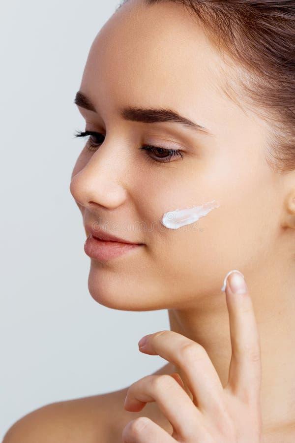 Cuidado de piel Señora que pone la crema de cara Photoset de la muchacha morena atractiva en fondo gris fotografía de archivo libre de regalías