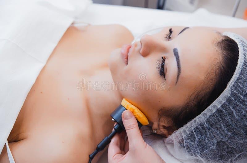 Cuidado de piel Terapia de Microcurrent Chica joven hermosa en los procedimientos para el cuidado de piel imagen de archivo libre de regalías
