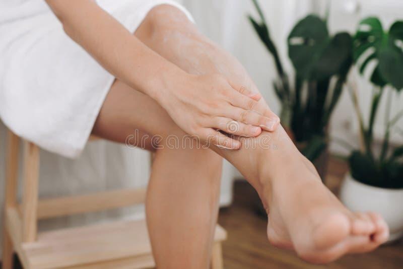 Cuidado de piel y concepto de la salud Mano de la muchacha con la crema de la crema hidratante que mancha las piernas para el res imagen de archivo