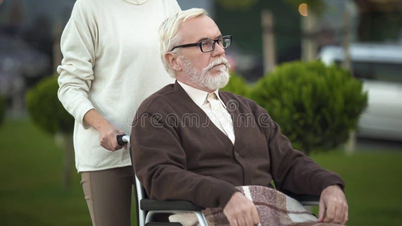 Cuidado de tomada fêmea da cadeira de rodas de primeira geração deficiente, auxílio da família, ajuda imagens de stock