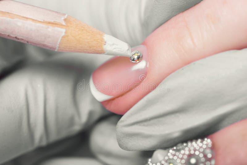 Cuidado del clavo del finger del primer del especialista de la manicura en salón de belleza imagen de archivo libre de regalías