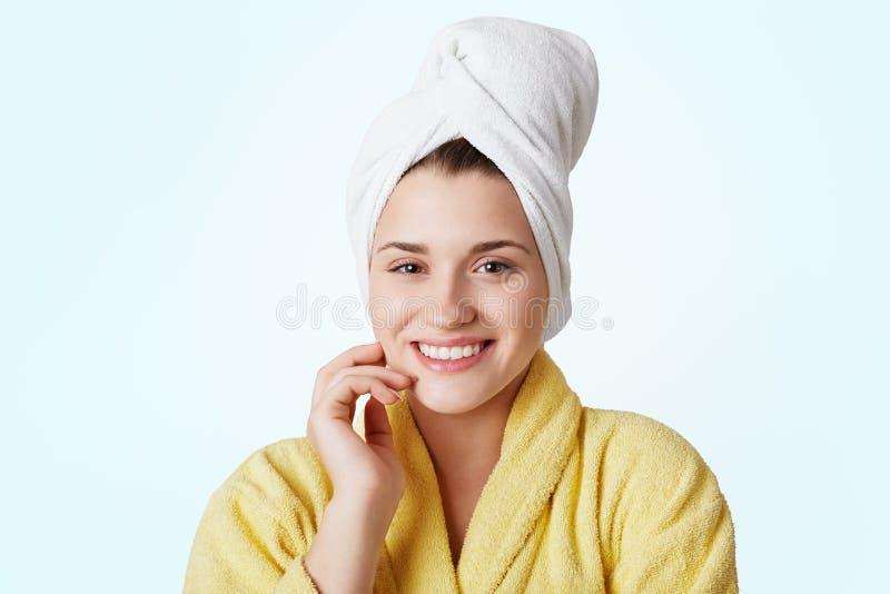 Cuidado del cuerpo y concepto del balneario La mujer joven bastante hermosa lleva la albornoz amarilla y la toalla en la cabeza,  imagen de archivo