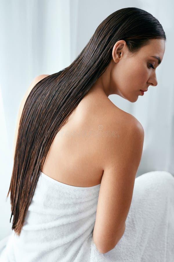 Cuidado del pelo y del cuerpo Mujer con el pelo largo mojado envuelto en toalla fotos de archivo