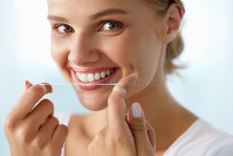 Cuidado dental Mulher com sorriso bonito usando o Floss para os dentes imagem de stock