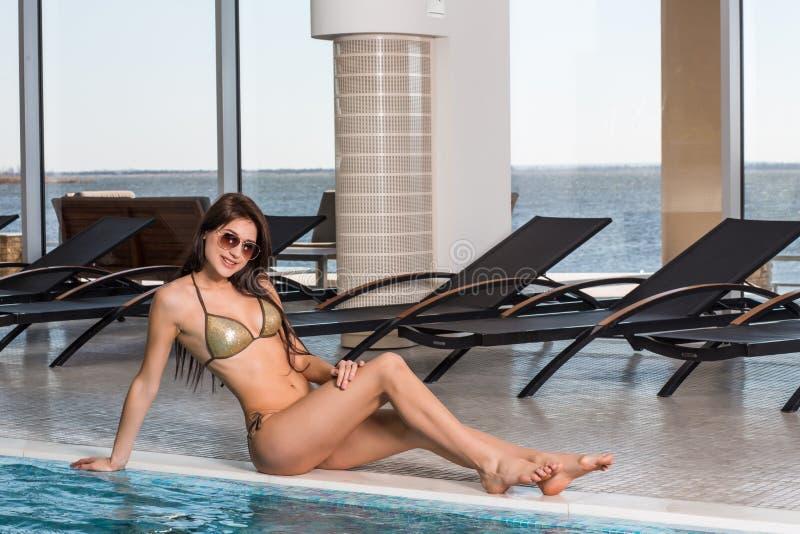 Cuidado do corpo Mulher com corpo perfeito no biquini que encontra-se perto do deckchair pela piscina fotos de stock royalty free