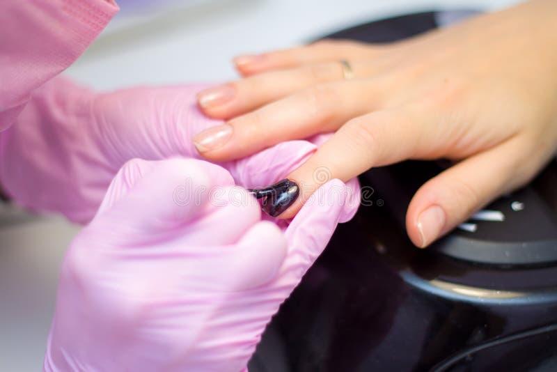 Cuidado do prego e conceito do tratamento de mãos As mãos do manicuro do close up em luvas cor-de-rosa estão pintando o verniz pa fotos de stock