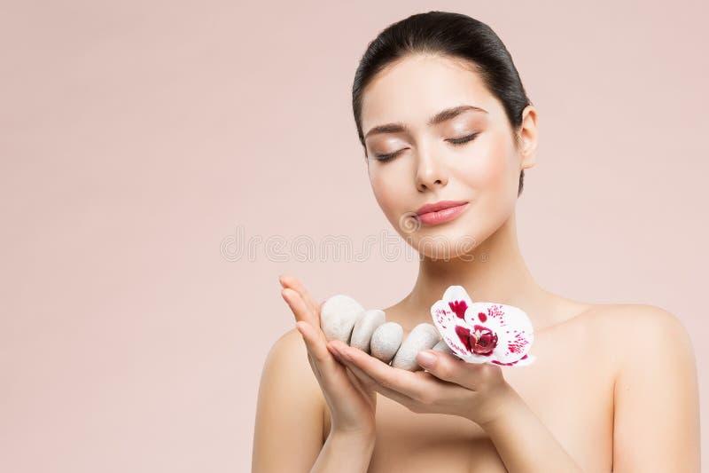 Cuidado e tratamento da beleza da mulher, modelo bonito Holding Massage Stones e flor da orquídea nas mãos, sonhos felizes da saú fotografia de stock