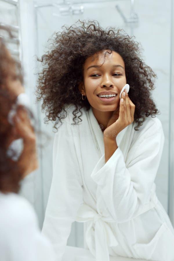 Cuidado facial de la piel. Chica quitando maquillaje con toallita de algodón en el baño imagenes de archivo