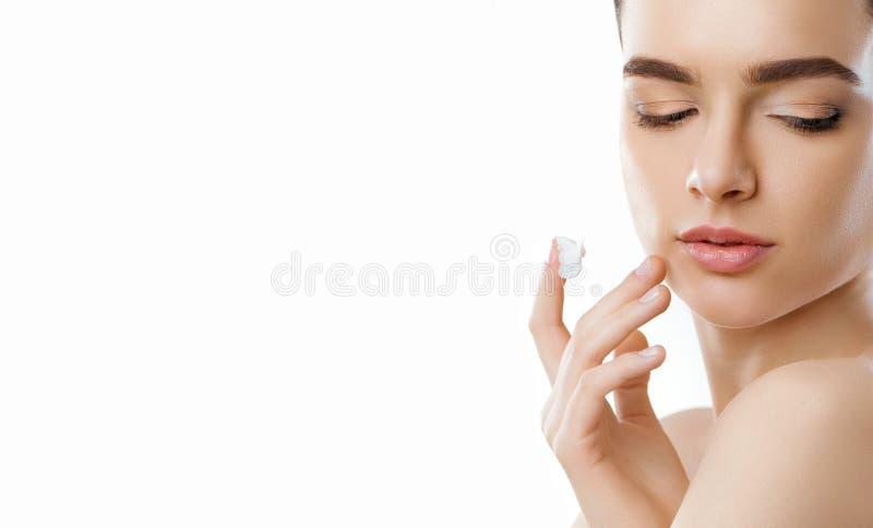 Cuidado facial F?mea que aplica o creme Face da beleza Retrato da jovem mulher Close up da menina bonita com o produto de beleza  imagem de stock