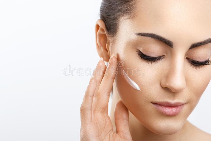Cuidado facial Hembra que aplica la crema Retrato de la mujer joven con crema cosm?tica en piel Primer de la muchacha hermosa con fotografía de archivo