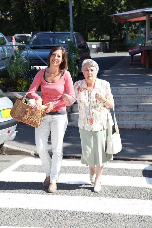 Cuidador casero con la persona mayor en ciudad imagen de archivo