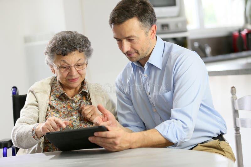 Cuidador casero que enseña una mujer mayor a cómo utilizar una tableta imagenes de archivo