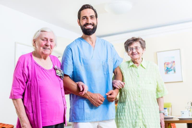 Cuidador com as mulheres superiores no lar de idosos imagens de stock