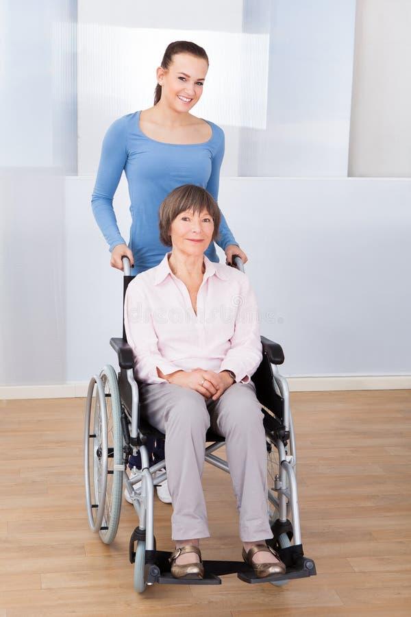 Cuidador com a mulher superior dos enfermos na cadeira de rodas imagem de stock