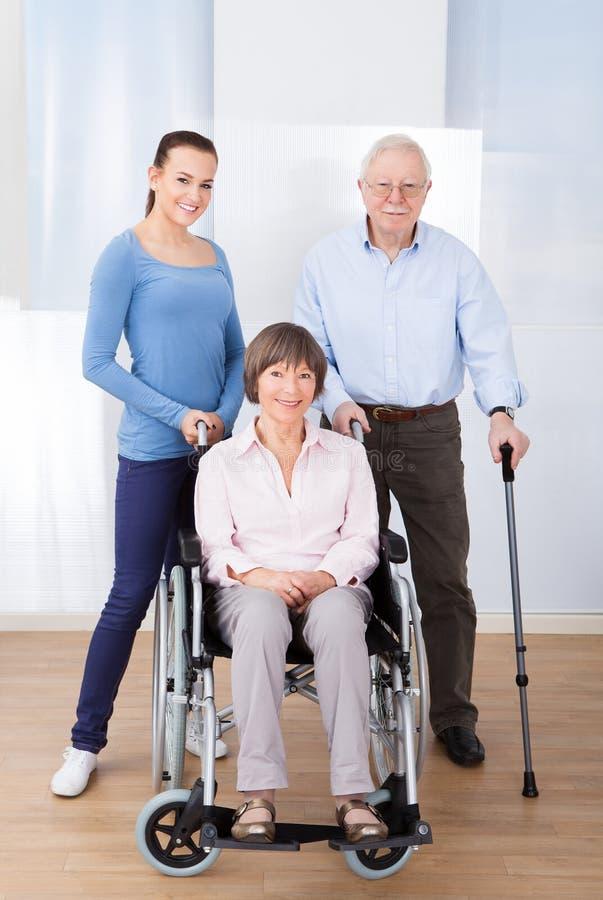 Cuidador con los pares mayores discapacitados imagenes de archivo