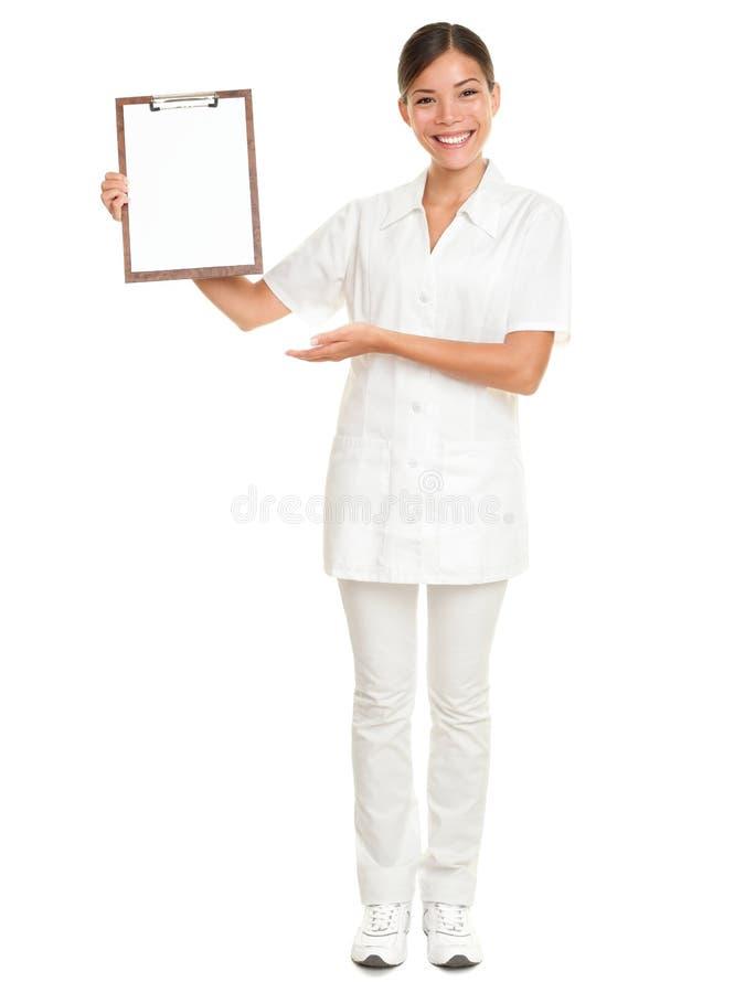 Cuidador de la enfermera que muestra la muestra del blanco del sujetapapeles fotografía de archivo libre de regalías